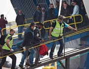 Grenzschutzbeamte begleiten einen Flüchtling auf eine Fähre. (Bild: Petros Giannokouris/AP (Lesbos, 8. April 2016))