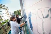Christian Rebecchi (vorne) und Pablo Togni bemalen die Neubad-Fassade. (Bild: Roger Grütter)
