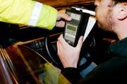 Ein Autofahrer muss ins Alkohol-Messgerät blasen. (Symbolbild Keystone)