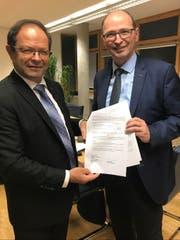 Regierungsrat Josef Hess (links) nimmt vom Direktor des Bundesamts für Umwelt, Marc Chardonnens, die Subventionsverfügung für das Projekt Hochwassersicherheit Sarneraatal, Teilprojekt Stollen Ost, in Höhe von 74,8 Millionen Franken entgegen. (Bild: PD)