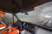 Ein Lokführer sitzt in einem Minibus auf einem Transportzug und bedient den Zug per Fernbedienung. (Bild: Keystone)