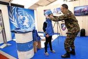 Hauptmann Beat Haenni kleidet Sonya als UNO-Militärbeobachterin ein.Bild: Werner Schelbert (Zug, 22. Oktober 2016)