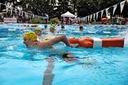 Ein jugendlicher Rettungsschwimmer von der SLRG Luzern zieht eine Puppe durch das Becken (oben). Fröstelnde Zuschauer beobachten einen Wettkämpfer beim Rettungsballwerfen. (Bilder Nadia Schärli)