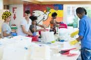 Junge Asylsuchende im Jugendwohnheim Waldheim bei der Arbeit am Kunstwerk «Unterwegs», eine aus Gipsfüssen bestehende Installation. (Bild: Dominik Zietlow)