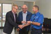 Regierungsrat Heinz Tännler (links) übergibt den Schlüssel an Beat Baumgart, Chef Polizeiregion Ennetsee (rechts) und den Chamer Gemeindepräsidenten Bruno Werder. (Bild: Zuger Polizei)