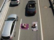 Zwei Ferienreisende haben es sich am Freitag beim Stau auf der A2 zwischen Erstfeld und Göschenen gemütlich gemacht. (Bild: /KEYSTONE/URS FLUEELER)