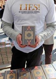 Ein Mitglied der «Lies!»-Bewegung präsentiert an einer Standaktion in Berlin einen Koran. (Bild: Getty/Adam Berry)
