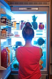 A young caucasian woman standing in front of the open refrigerator at late night, contemplating and wondering about a midnight snack in a domestic home kitchen. She is dressed in a bath robe hungry and looking for food. A symbol of dieting lifestyle. Photographed in vertical format. (Bild: YinYang (E+))