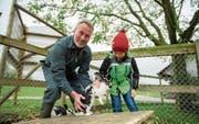 Pächter Josef Heer zeigt Besucher Danilo aus Luzern die Kaninchen auf dem Grämlishof. (Bild: Dominik Wunderli (Horw, 8. November 2017))