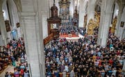 So voll war die Hofkirche Luzern wohl noch nie wie zum Abschluss der ersten Luzerner Chornacht: 500 Sänger vermengen sich mit dem Publikum nach dem gemeinsamen Auftritt unter der Chornacht-Initiantin Ulrike Grosch. (Bild: Philipp Schmidli)