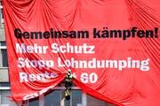 Trillerpfeifen, Fahnenmeer und Transparente gehören bei einer Demonstration dazu. Das Bild zeigt ein kletterndes Unia-Mitglied an einer Kundgebung von Bauarbeitern im vergangenen Juni in Zürich. (Bild: Keystone/Valeriano Di Domenico)
