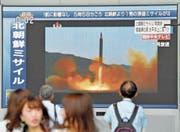Fussgänger betrachten vor einem TV-Sender die Bilder des nordkoreanischen Raketenstarts. (Bild: The Asahi Shimbun/Getty (Osaka, 29. August 2017))