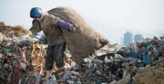 Eine Frau sammelt Plastikflaschen in einer Abfalldeponie in Dalian, um sie vom restlichen Abfall zu trennen. (Bild: Thomas Dooley/Getty (10. Januar 2008))