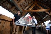 Die Initiativkomiteemitglieder Maurus Zeier (links) und Fabian Reinhard gestern mit einer der Bildkopien auf der Kapellbrücke. (Bild: Manuela Jans / Neue LZ)