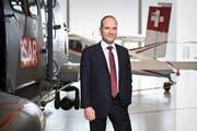 Ruag-CEO Urs Breitmeier postiert in Emmen vor einem Superpuma und einem Pilatusporter. Bild: Manuela Jans-Koch (Emmen, 20. März 2014)
