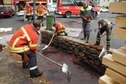 Einsatzkräfte der Feuerwehr schaufeln Öl. (Bild Kantonspolizei Schwyz)