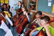 Mitglieder des Orchesters BaBeL-Strings bei einer Probe im Luzerner St.-Karli- Schulhaus. Mitgründerin Graziella Carlen spielt im Hintergrund mit. (Bild Nadia Schärli)