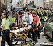 Rettungskräfte transportieren Verletzte ab, nachdem ein Auto in die Menschen raste. Bild: Steve Helber/AP (Charlottesville, 12. August 2017)