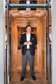 CEO Thomas Oetterli (46) in einem holzverkleideten Schindler-Lift. Bild: Roger Grütter (Ebikon, 26. Oktober 2016)