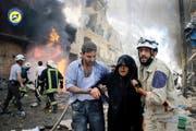 Helfer begleiten eine Frau aus den Trümmern nach einem Luftangriff in der syrischen Stadt Aleppo am 8. Juni 2016. (Bild: AP)