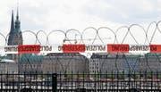 Stacheldraht wurde installiert, um Demonstranten am G20-Gipfel in Hamburg in Schach zu halten (oben). Beim Treffen, das Spannungen verspricht, sind unter anderem dabei: Der türkische Präsident Recep Tayyip Erdogan, die deutsche Kanzlerin Angela Merkel, US-Präsident Donald Trump, Russlands Präsident Wladimir Putin, Frankreichs Präsident Emmanuel Macron und der chinesische Präsident Xi Jinping (von links). (Bilder: EPA/Keystone)