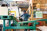 Ein Sägewerkmitarbeiter überwacht die Bearbeitung von Bauholz auf einer Hobelmaschine. Bild: Christian Beutler/Keystone (Unterstammheim, 7. März 2016)