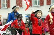 Mit Fahnen und Alpenrosen durch das Schneegestöber: Brauchtum will gepflegt sein. (Bild: Adrian Venetz / Neue OZ)