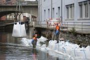 Die Bauarbeiter erstellen mit schweren Säcken eine Wasserhaltung. (Bild: Maria Schmid)