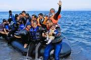 Syrische Flüchtlinge kommen aus der Türkei per Schlauchboot auf der griechischen Insel Lesbos an. Derzeit erreichen täglich bis zu 3000 Flüchtlinge die Insel. (Bild: EPA/Orestis Panagiotou)