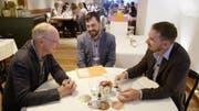 Diskutieren an einem Tisch an der wöchentlichen Sitzung bei Remimag: Peter Eltschinger (links) mit seinen Söhnen Bastian und Florian. (Bild: SRF)