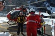 Der Rega-Helikopter steht bereit, während Ärzte einen Patienten verladen. (Bild: Christoph Riebli / Neue LZ)