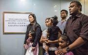 Vanessa Rodel (links) mit Tochter Keana, Ajith Pushpa (hinten Mitte) sowie das Ehepaar Nadeeka (vorne Mitte) und Supun Thilina mit ihren Töchtern Dinath (rechts) und Sethumdi vor einer Beschwerdeinstanz in Hongkong, die Klagen wegen Folter untersucht. (Bild: Isaac Lawrence/AFP (17. Juli 2017))