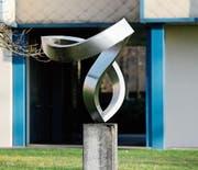 Die Stahlblechplastik «Zigi Zagi» von Josef Staub war 1983 eine Schenkung an die Stadt Zug. Das Kunstwerk ist auf einer Betonkonsole fixiert und steht auf der Wiese hinter dem Hertizentrum.