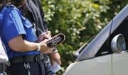 Eine Polizeiassistentin stellt eine Ordnungsbusse aus. (Symbolbild ZZ)