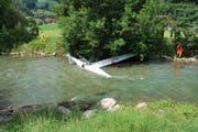 Einsatzkräfte sichern den Segelflieger in der Sarneraa mit Seilen. (Bild: Polizei Obwalden)