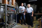 Hermann (r.) und Armin Röllin prosten sich mit einem preisgekrönten Destillat aus ihrer Brennanlage zu. (Bild: Stefan Kaiser)