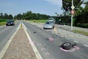 Räder und Trümmerteile der schrottreifen Autos liegen auf der Sinserstrasse. (Bild: Zuger Polizei)
