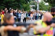 Durch Polizisten mit Waffen abgeschirmt, verlassen unzählige Menschen am Freitagabend das Olympia-Einkaufszentrum in München. (Bild: AFP)