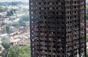 Feuerwehrmänner untersuchen die Fassade des komplett zerstörten Hochhauses. (Bild: Frank Augstein/AP (15. Juni 2017, London))