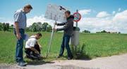 Daniel Schillig, Präsident des Vernetzungsprojekts, Landwirt Richard Zurbrügg und Dominik Iten, Präsident des Zuger Vogelschutzes (von links) montieren eine Infotafel bei der Zufahrtsstrasse zum Hof Frohbüel. (Bild: Maria Schmid (Menzingen, 3. Juli 2017))