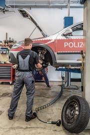 Ein Mitarbeiter wechselt in der Polizeiwerkstatt Bremsscheiben aus. (Bild: Nadia Schärli (Emmen, 24. August 2017))