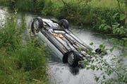 Das Auto landete auf dem Dach m Kanal. (Bild: Zuger Polizei)
