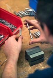 Ein Mitarbeiter von SIG in Neuhausen am Rheinfall montiert am 4. Mai 2004 ein Metallbauteil. Bei SIG werden Getraenkeverpackungen aus Karton und Verschlusssysteme entwickelt und hergestellt. (KEYSTONE/Gaetan Bally) (Symbolbild: Gaetan Bally / Keystone)