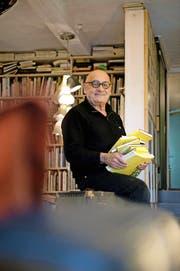 Tino Steinemann (70) mit einem von über 200 Reiseskizzenbüchern in seinem Zuhause in Neuenkirch. (Bild Dominik Wunderli)