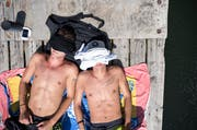 Um einen kühlen Kopf zu bewahren, haben diese Jugendlichen am Donnerstag ihre T-Shirts aufs Gesicht gelegt. (Bild: Keystone)