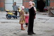 Unter Druck: Uiguren in der chinesischen Provinz Xinjiang. (Bild: Ng Han Guan/AP (Aksu, 17. Juli 2014))