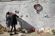 Zwei Mädchen schreiben Beileidsbekundungen auf eine Wand in der Nähe des zerstörten Hochhauses. (Bild: Alastair Grant/AP (15. Juni 2017, London))