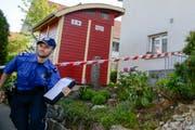 Ein Polizeibeamter vor dem abgesperrten Grundstück in Würenlingen. (Bild: Keystone)