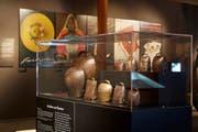 Die Ausstellung zeigt unter anderem eine Auswahl von Carigiets Plakaten. Im Vordergrund: Vitrine mit Schellen und Glocken aus dem Kanton Graubünden. (Bild: Mara Truog/Schweizerisches Nationalmuseum/Alois Carigiet Erben)