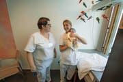 Gefreite Gioia Diggelmann (rechts) lässt sich von Abteilungsleiterin Regula Furger den Umgang mit Neugeborenen zeigen. (Bild: Dominik Wunderli / LZ)